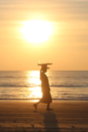 a woman carrying a tray on her head in the sunset