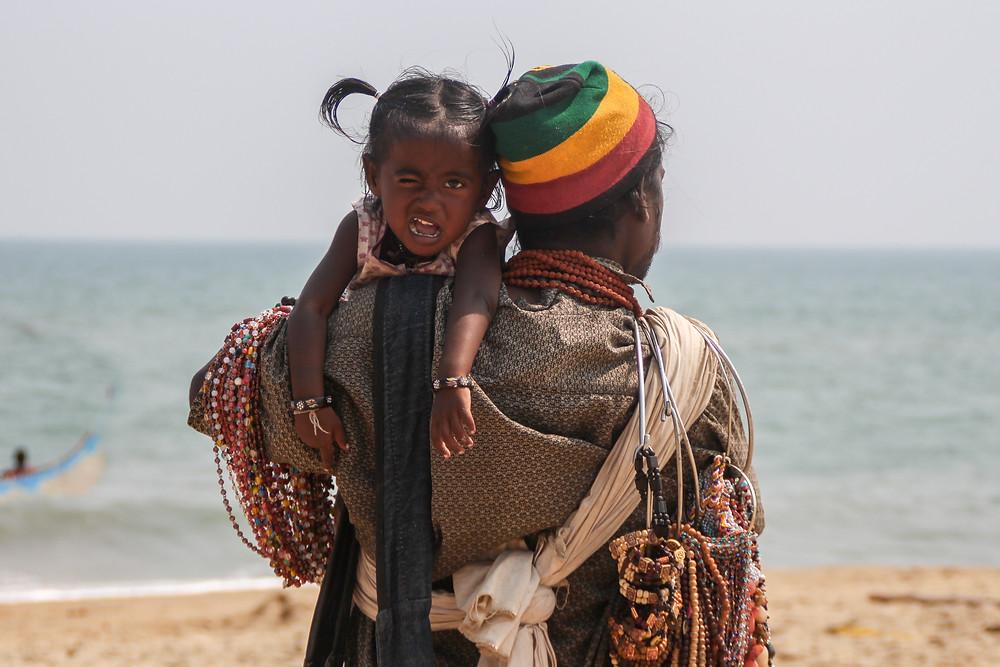 מוכר תכשיטים הודי מחזיק את הבת שלו שקורצת למצלמה