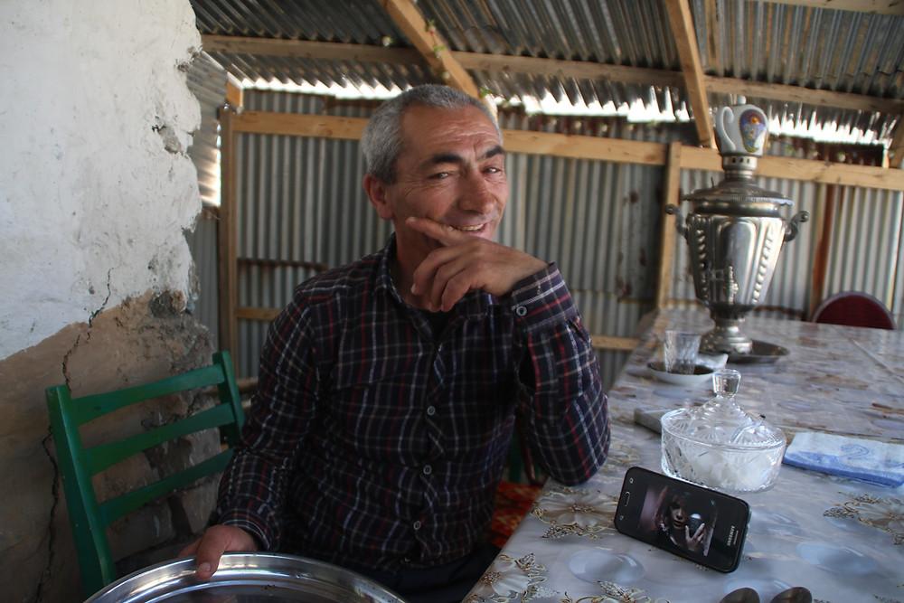 רחמן מביט למצלמה, לצידו טלפון עם קליפ של יסמין לוי
