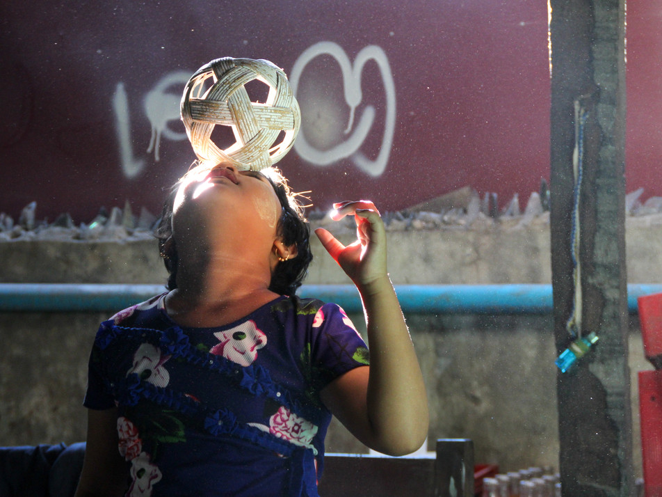 A girl playing with a Chinlone ball
