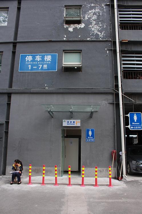 a woman sitting outside public toilets in Beijing