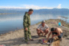kyrgyz men preparing food in toktogul reservoir