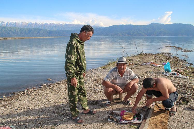 kyrgyz men preparing food in toktogul reservoir