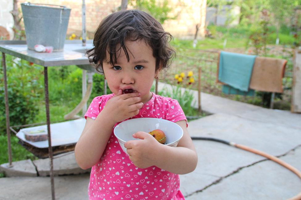 kyrgyz girl eating fruits