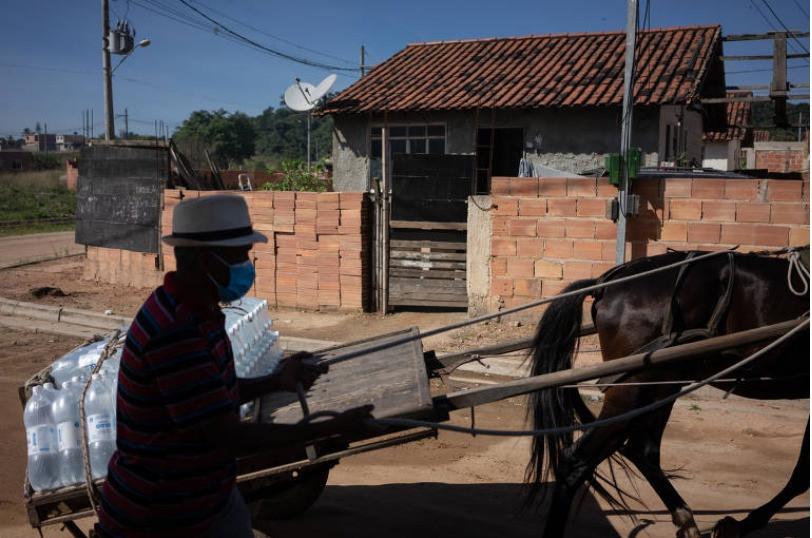 Sem caminhão para realizar as entregas, centro cultural da comunidade  Cinco Marias, na zona oeste do Rio, teve que recorrer a José Roberto, 56  anos, dono de uma carroça Tércio Teixeira/Folhapress/