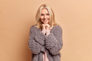 fashionable-blonde-forty-years-old-woman-keeps-hands-chin-smiles-gently-wears-warm-winter-
