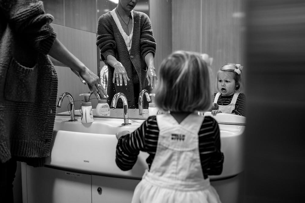 Clara makes a face while Erinn washes hands