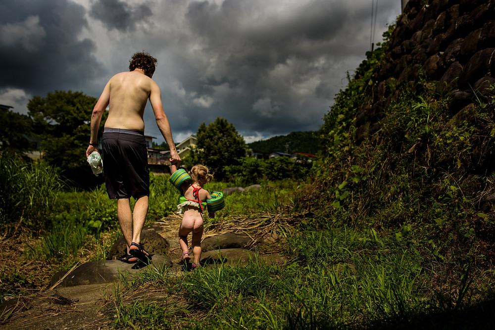 Brad and a diaper-less Skye walk along the grassy path