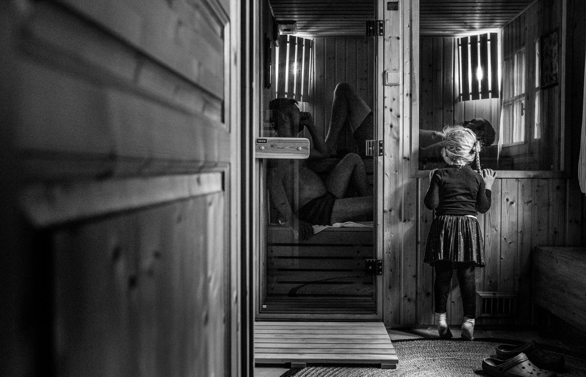little girl peeks into the sauna