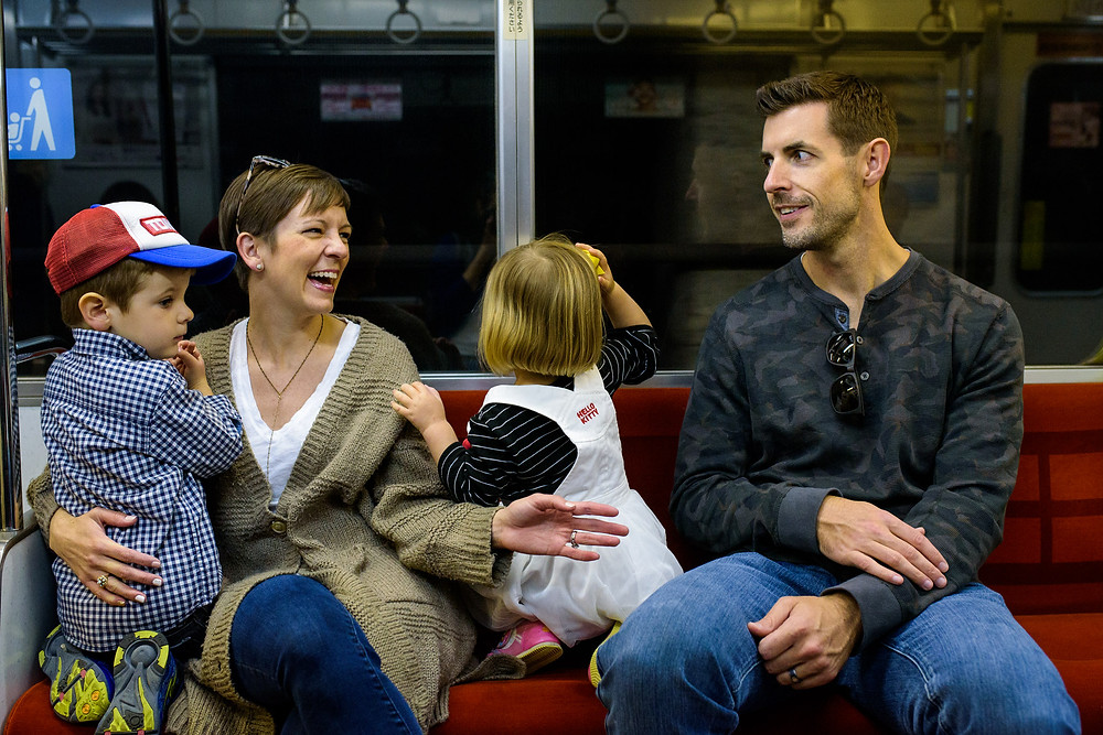 Erinn and Justin laugh on the subway