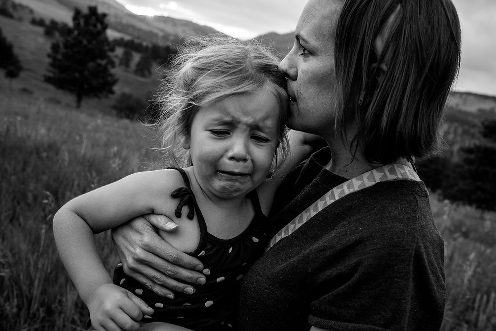 sad little girl crying in her mom's arms