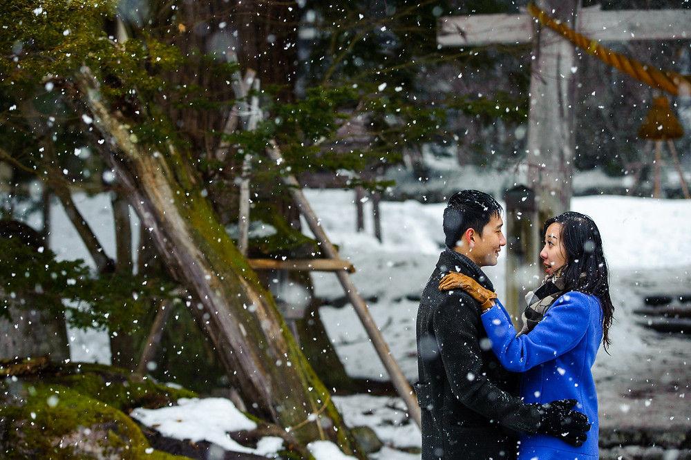 Snow falls around the couple