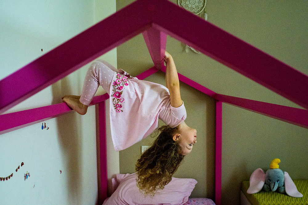 little girl climbs on her bed