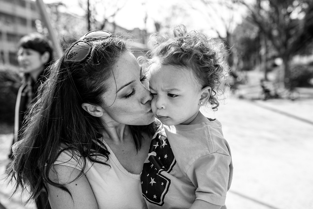 Gia grimaces during a kiss from mommy