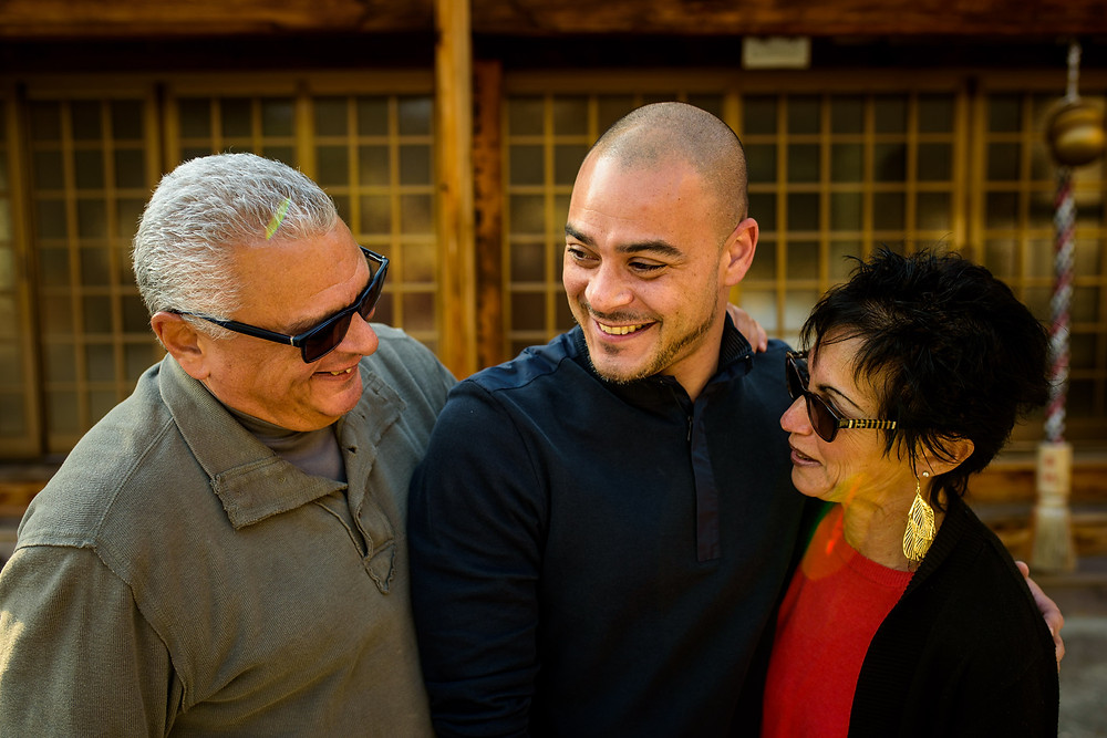 Brian and his parents laugh together at the shrine