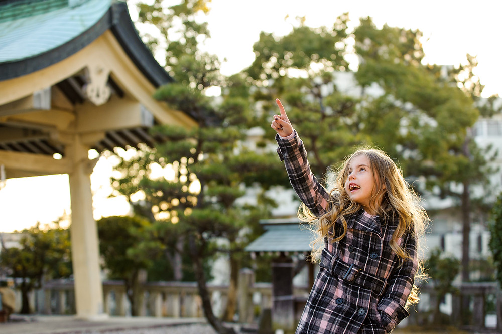 Amelia points to the sky at the shrine