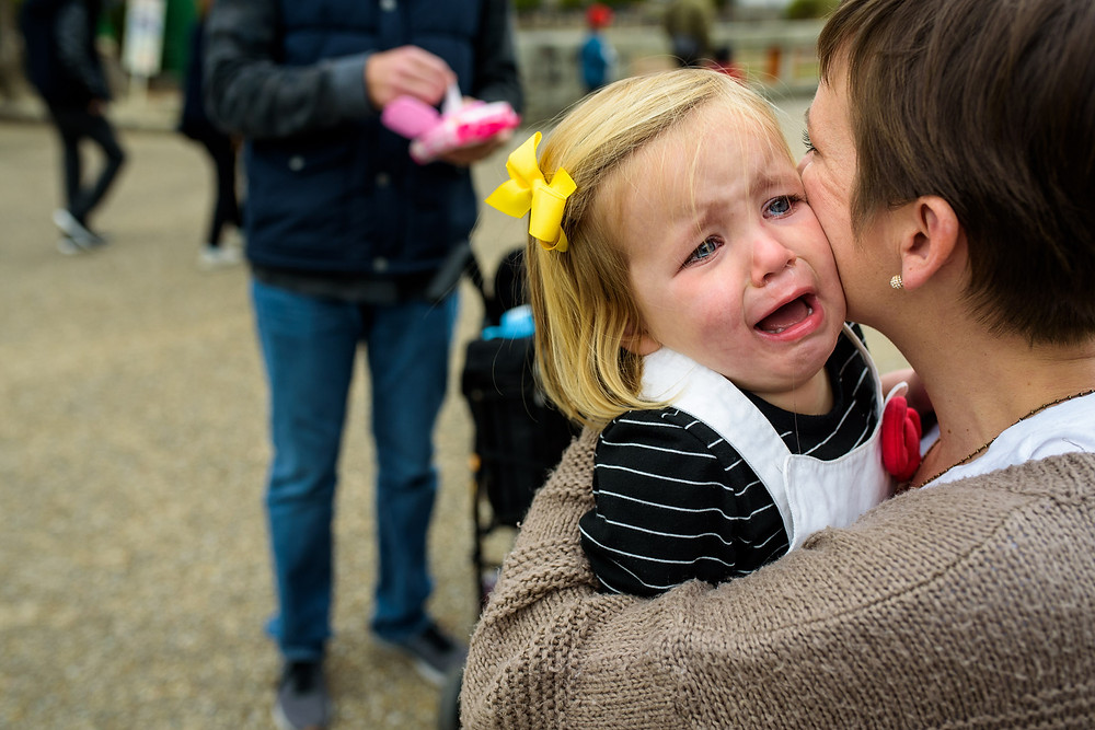 Clara cries on her mother's shoulder
