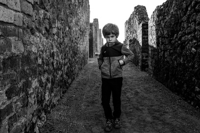 boy chews his sweater as he explores Pompeii ruins