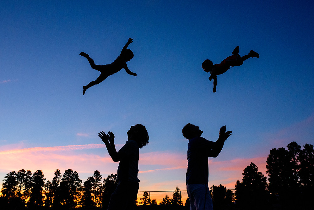 Two kids thrown in the air at sunset in Colorado