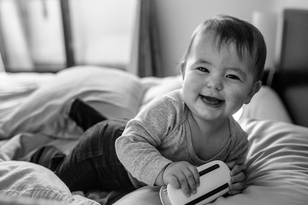 Taiyo, who is getting more and more mobile, smiles and laughs as he scoots on the bed