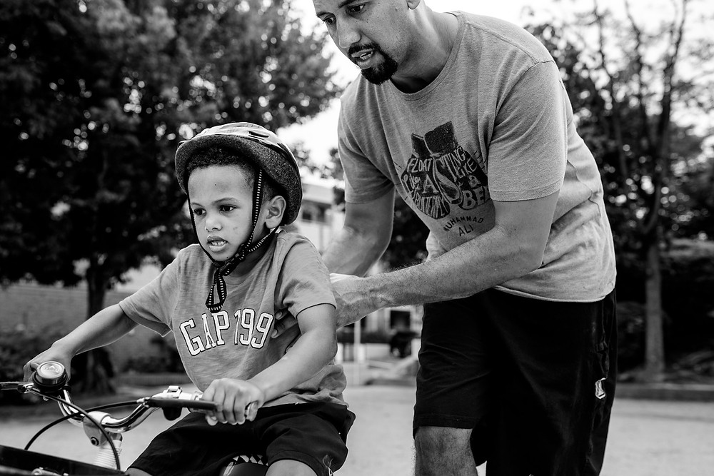 Father teaches his son to ride his bike