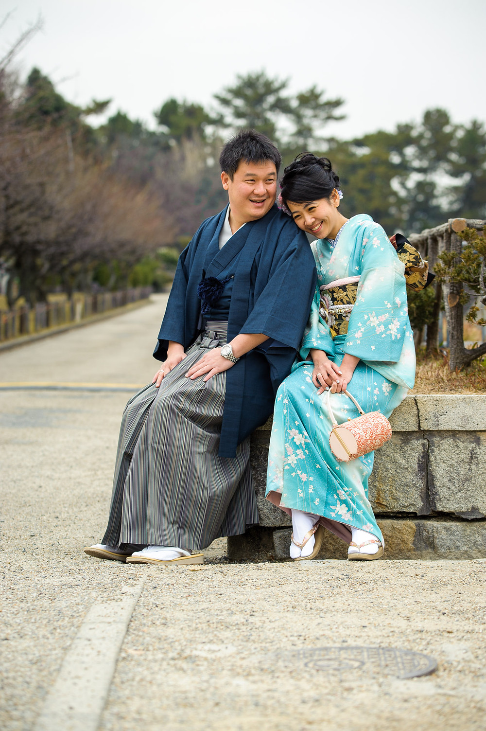 Carina and Very smile and laugh as they sit together in front of the castle in their kimonos