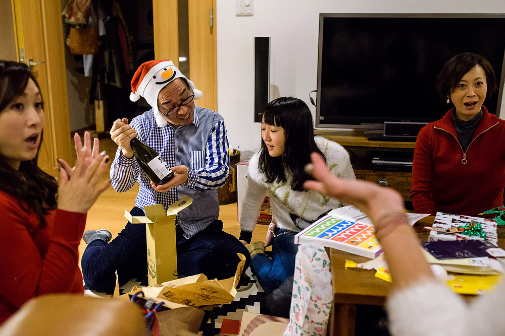 Neighbors open gifts. Erinn found a very rare and special bottle of Sake for Tatsuaki.