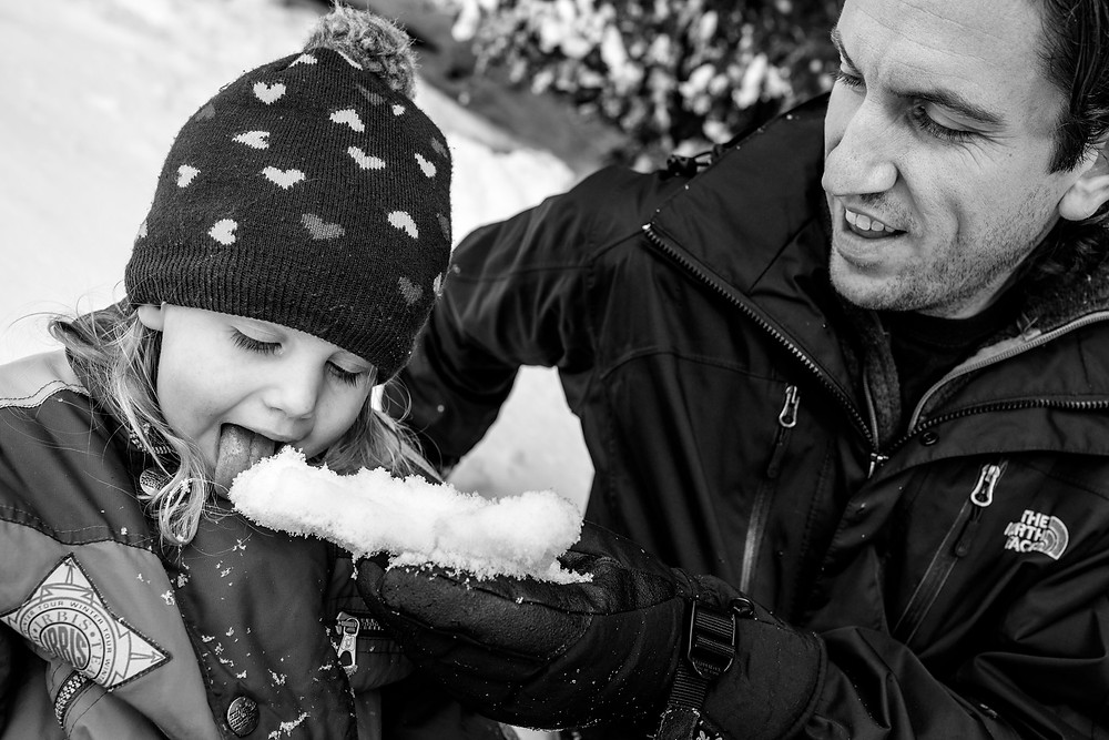dad feeding his child snow