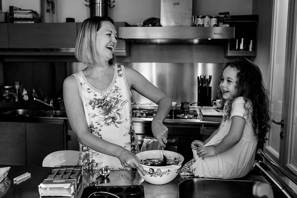 mom and her little girl laugh while baking together