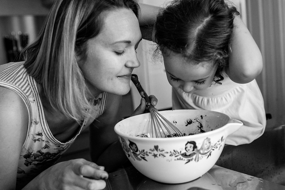 mom and her little girl make cupcakes