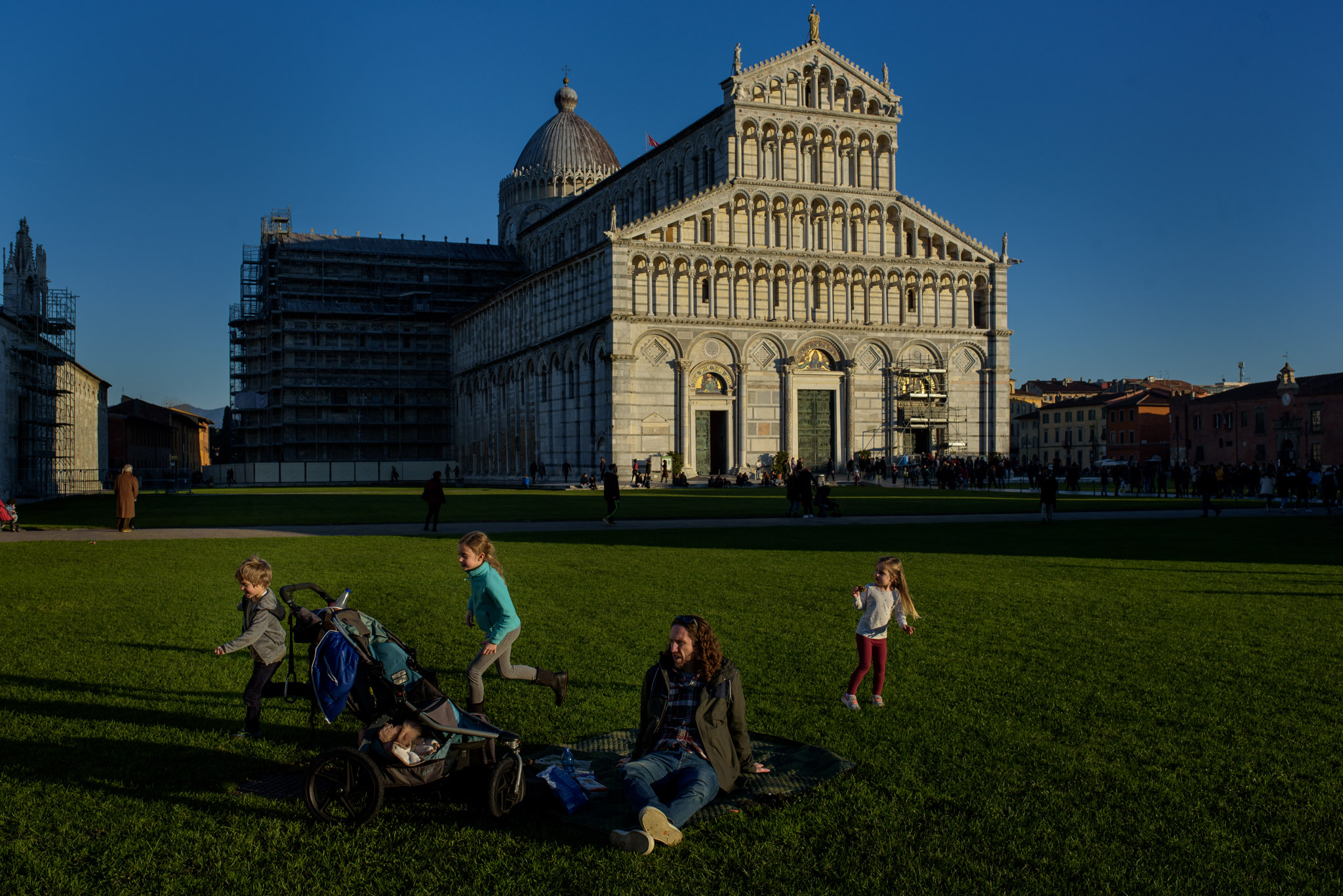 kids play, dad sits in front of the cathedral in Pisa