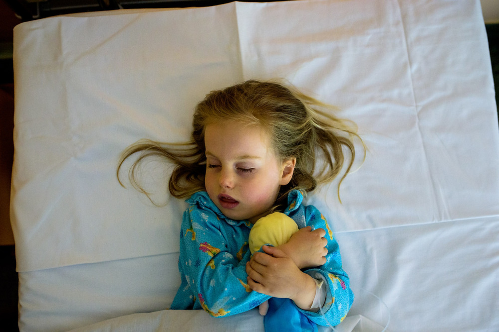 cuddling with her elsa doll after surgery