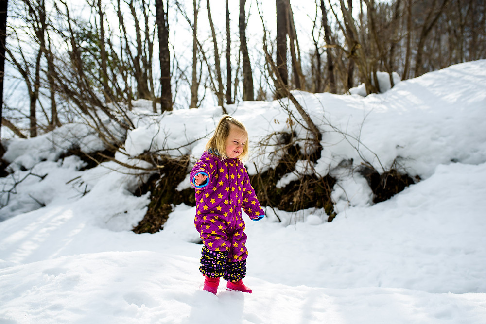 Skye stands crying in the  snow in her purple snowsuit