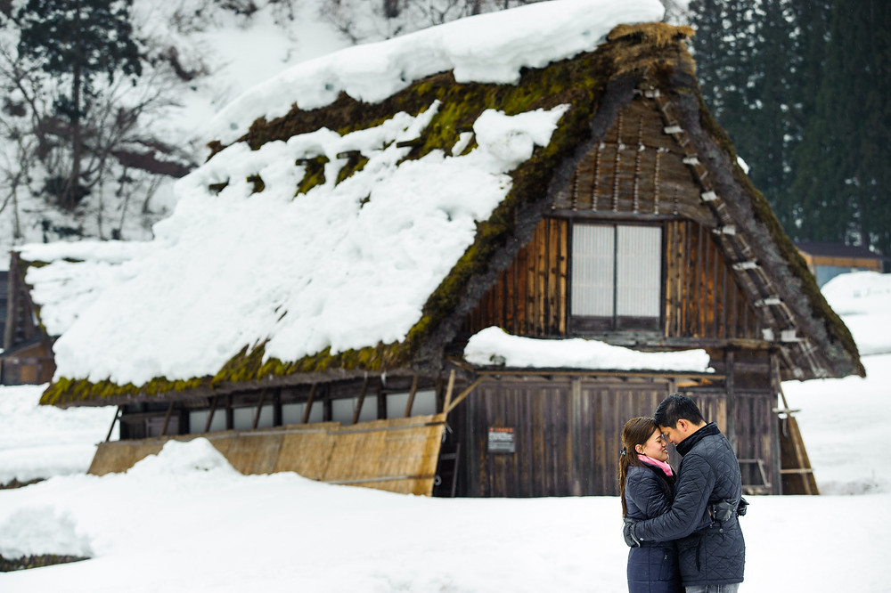 wide angle shot of a grass roof home in Shirakawago with a happily married couple standing in front