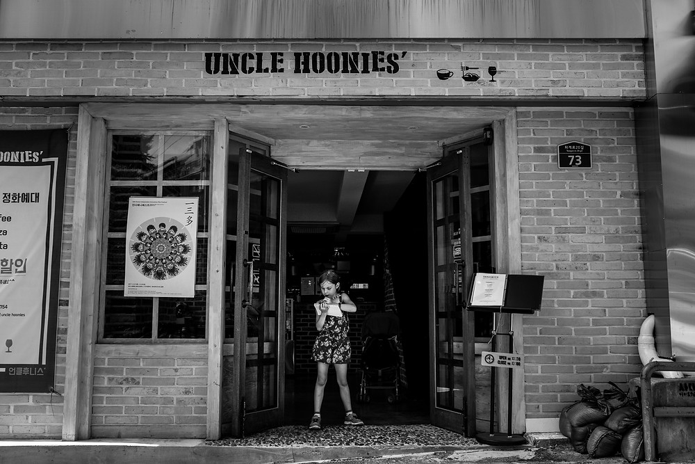 Amelia writes notes about our travels in the doorway of Uncle Hoonies in Seoul