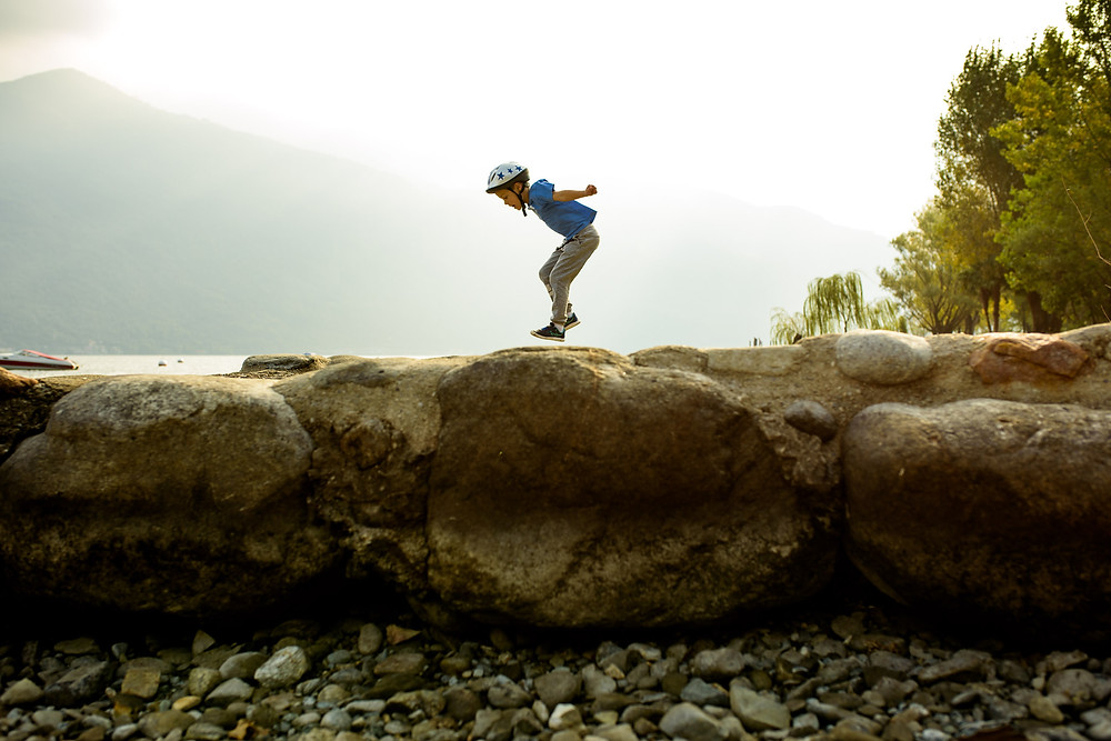 boy jumps across big rocks