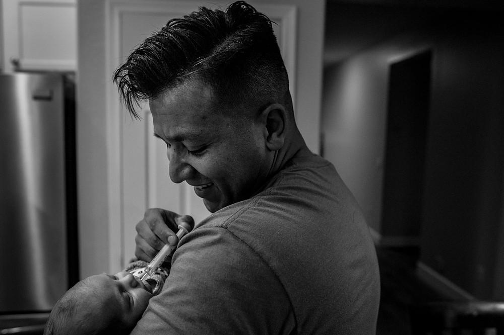 Dad feeds baby her medicine