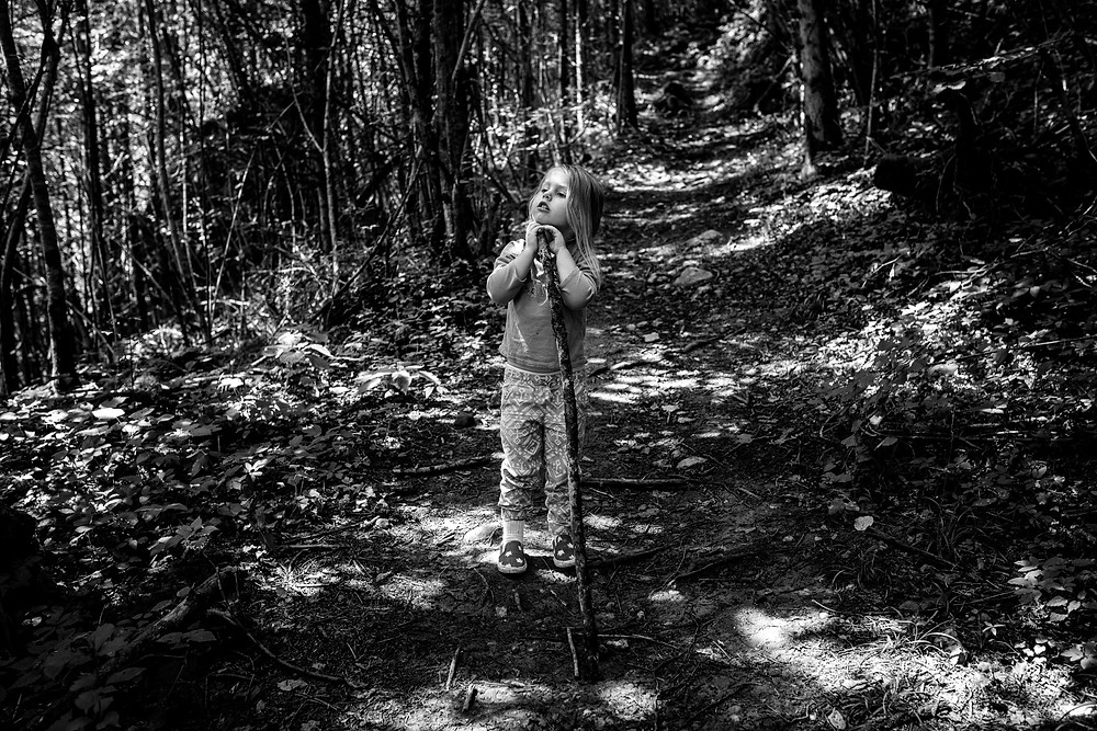 little girl hiking with a big hiking stick