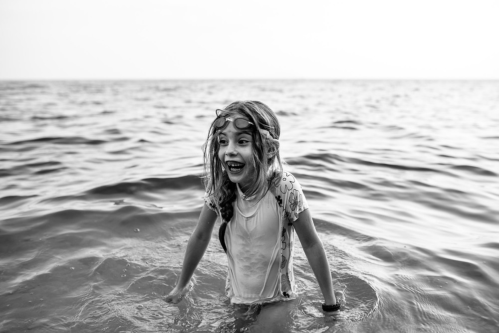 Amelia laughs as she wades in the ocean water