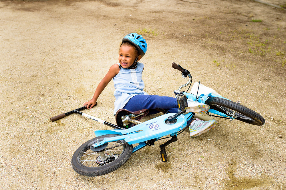 Addison falls off the bike happily