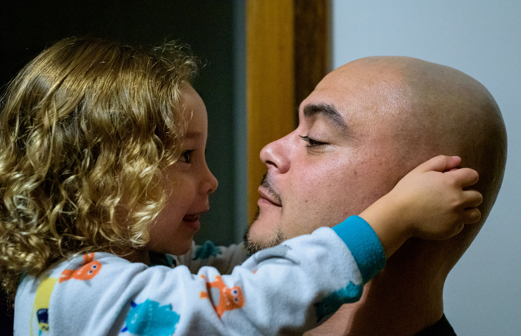 girl holds daddy's ears