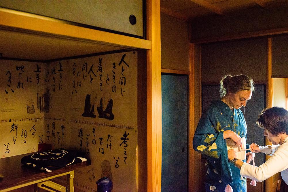Woman in a tatami room dressing in Kimono
