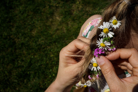 mom braids a girl's hair with flowers