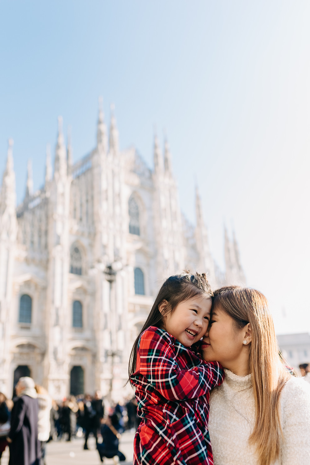 mom kisses daughter in front of the duomo
