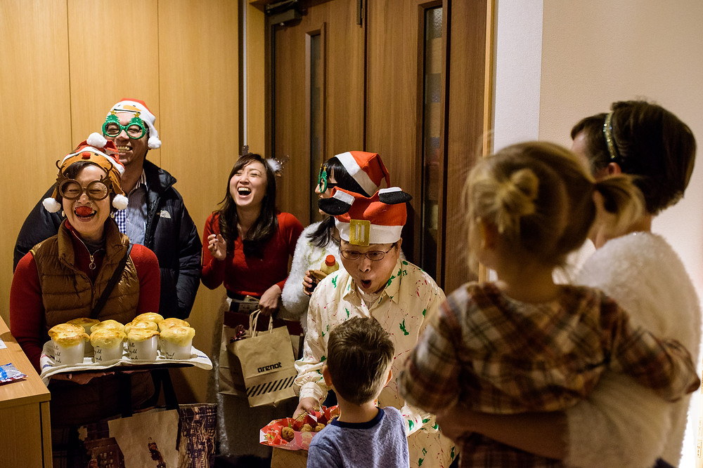 The neighbors arrive with food and presents, dressed for Christmas celebrations