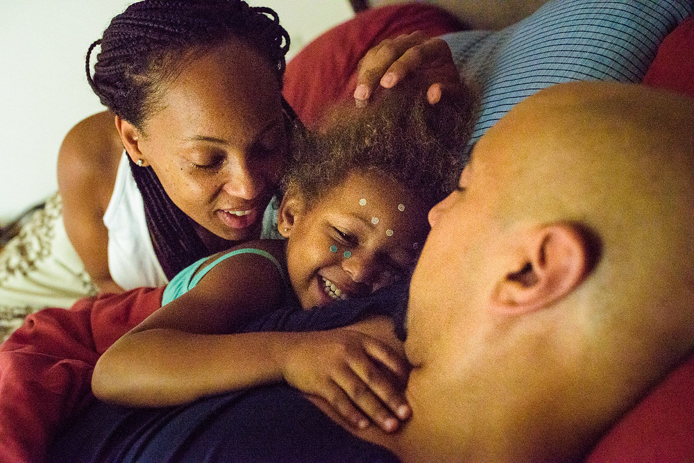 Addy and her parents cuddle