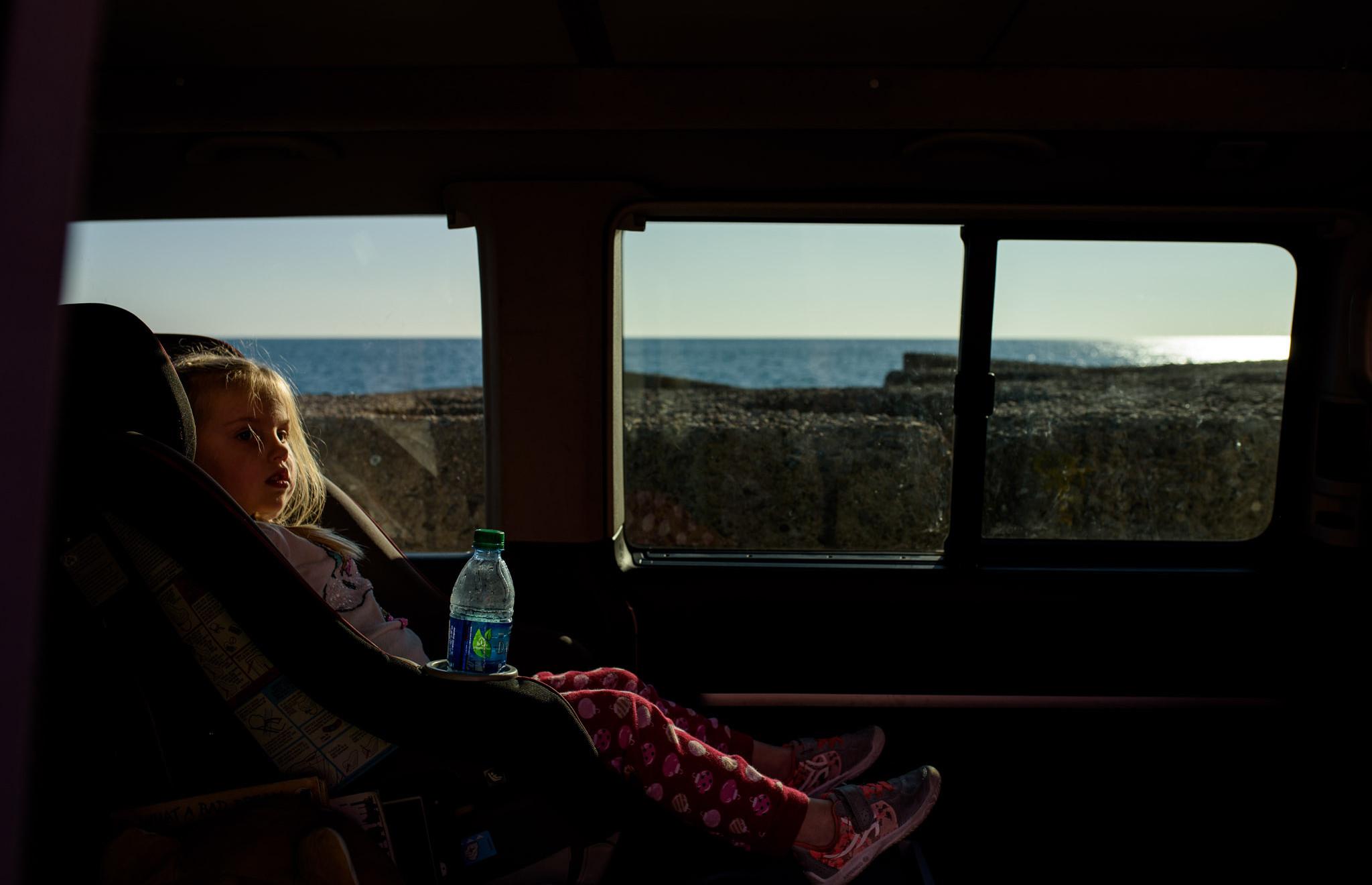 girl sits in her van carseat