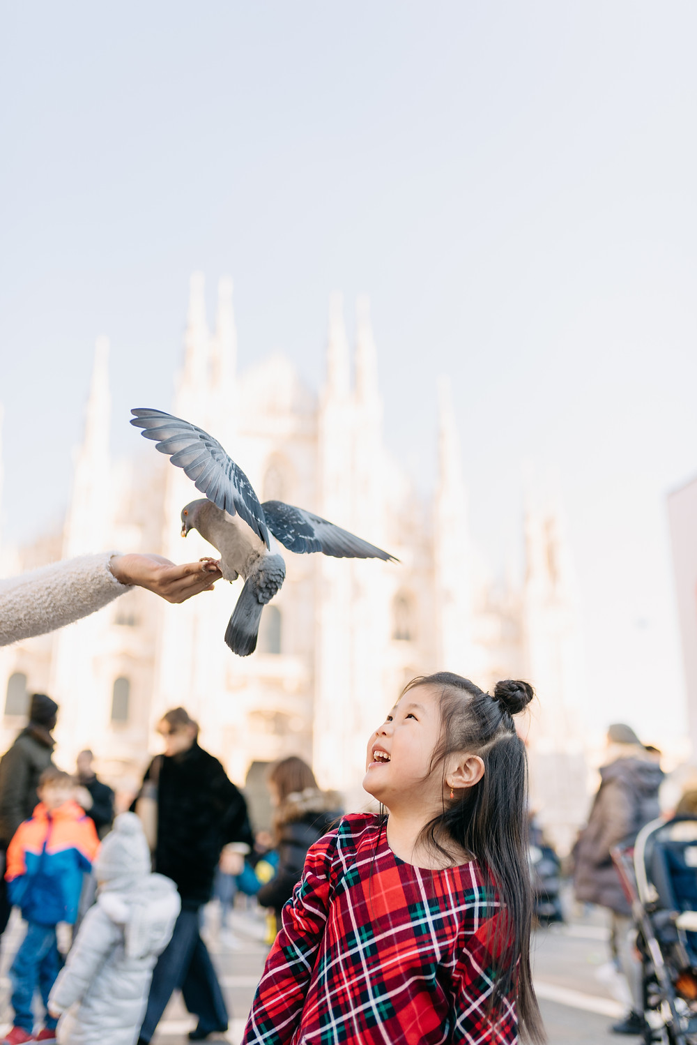 girl sees a bird sitting on her mom's hand at the duomo