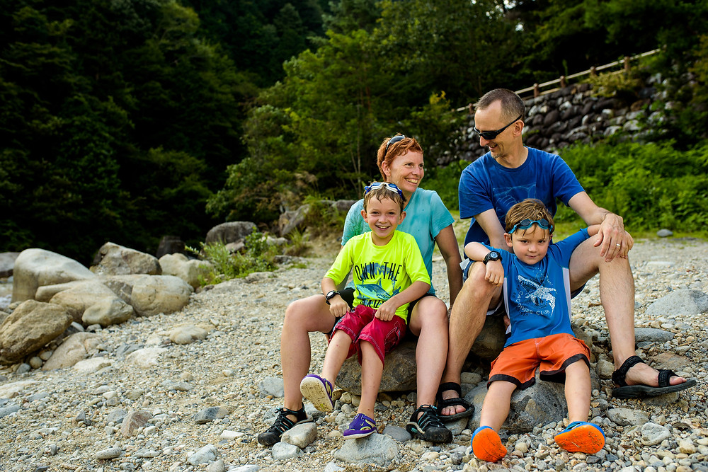 The family sits on the rocks and watches the river