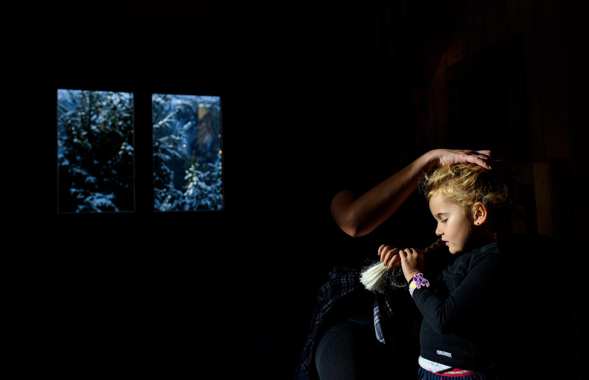 little girl gets an Elsa braid in a cabin
